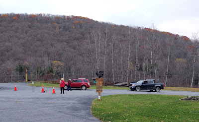 Two vehicles lined up for drive-thru Trick or Treating. Two museum staff are there to hand out goody bags. A tree-covered hill is in the background.