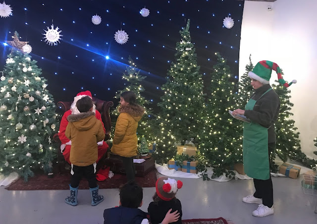 Children talking to father christmas and his elf at woodhorn
