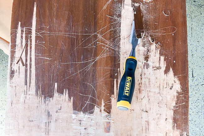 Using a chisel to scrape off and remove damaged veneer