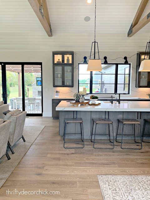 Great room with tall ceilings wood beams gray kitchen