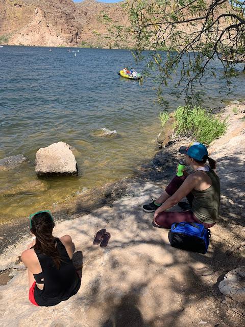 two women sitting on rocks near a lake