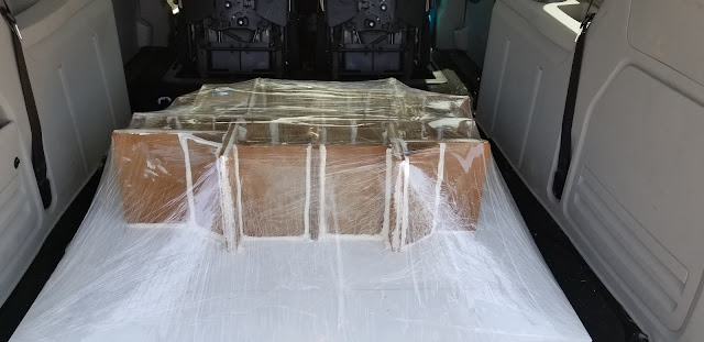 Back trunk of the car filled with boxes shrink wrapped.