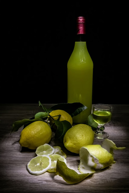 A picture of a bottle of limoncello, and lemons with the peel scattered around it