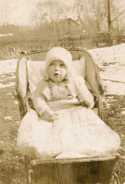 Unidentified baby in a carriage, bundled up. Snow on the ground. Dixon or Karvlious? Early 1900's.