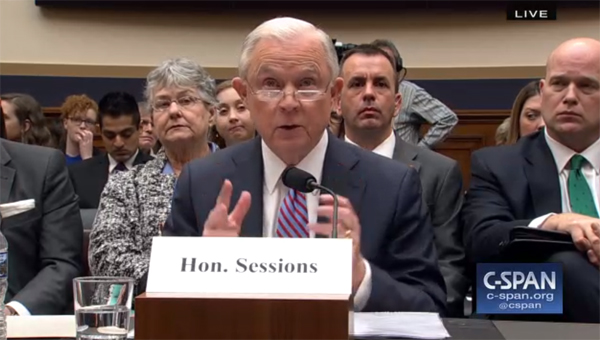 image of Jeff Sessions testifying, while an older white woman in the gallery behind him appears to be giving him the side-eye