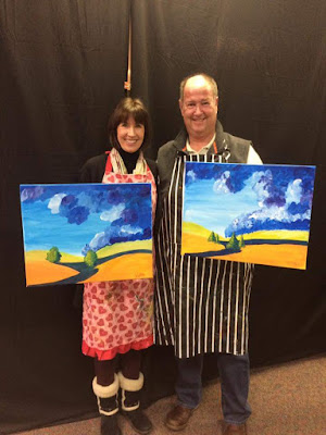 Couple holding paintings of mountains with path and trees