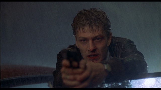 Sean Bean holding a gun while wet