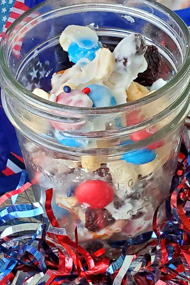 red white and blue festive snack mix in a mason jar
