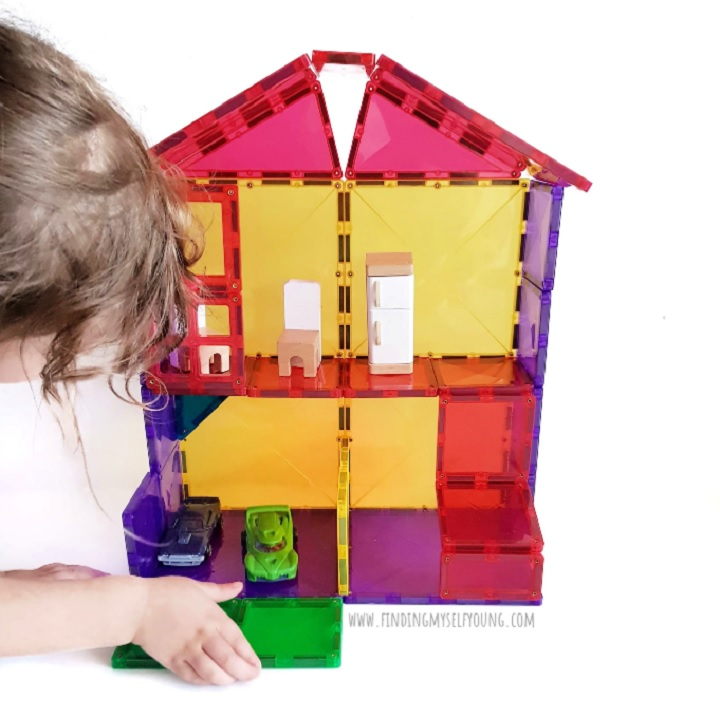 child making a magnetic tile doll house