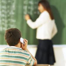 kid using cell phone in school with teacher in background