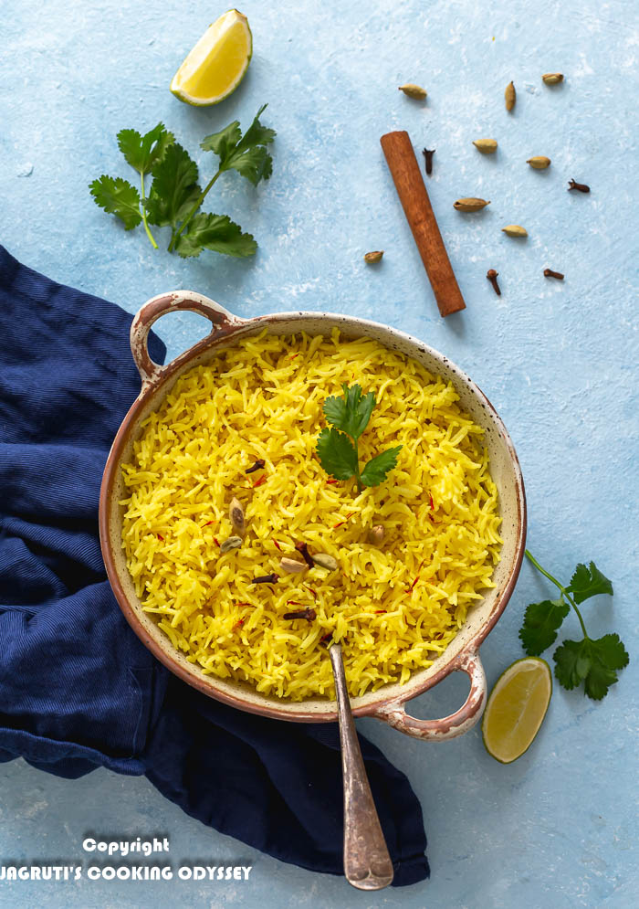 Takeaway style pilau rice or turmeric rice is in a ceramic container topped with whole spices and freshly chopped coriander.