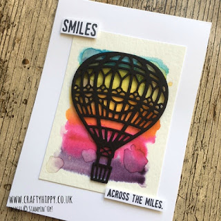 A white greetings card showing a die-cut black hot air balloon over a water-coloured rainbow background with the words 'smiles across the miles'