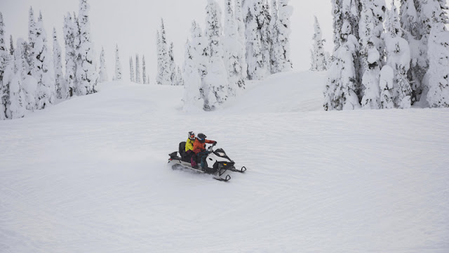 two snowmobile riders taking it slow on a wide groomed area