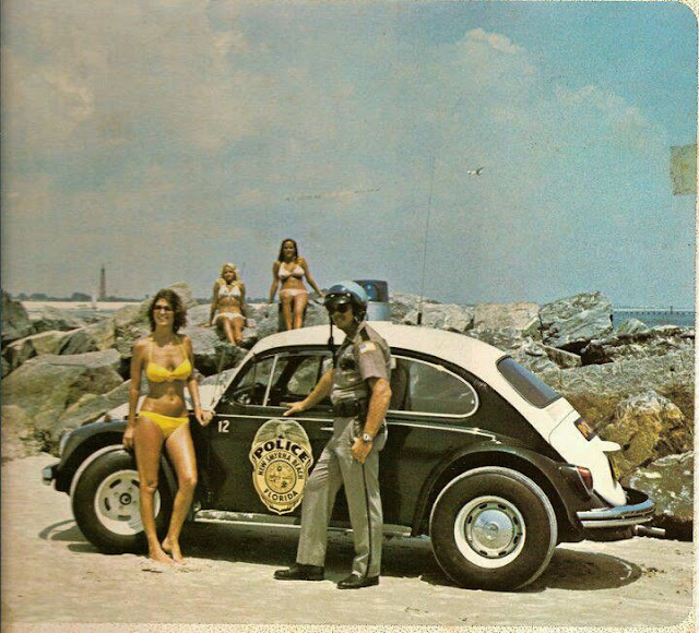 VW Bug Florida Police. An officer wearing his helmet, poses by the bug with three ladies in Bikinis. Hey Ladies. marchmatron.com