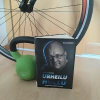 Urheiluhullu-kirja lattialla kahvakuulan vieressä, taustalla polkupyörän rengas