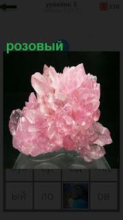 На постаменте на темном фоне лежит розовый кристалл