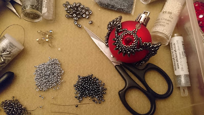 Bauble with red and grey crystal beads in-progress with scissors