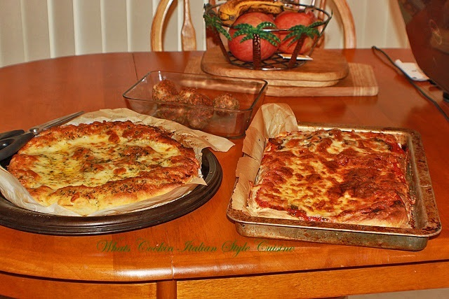 these are two pizzas cooling one round with garlic one square with tomato sauce and cheese