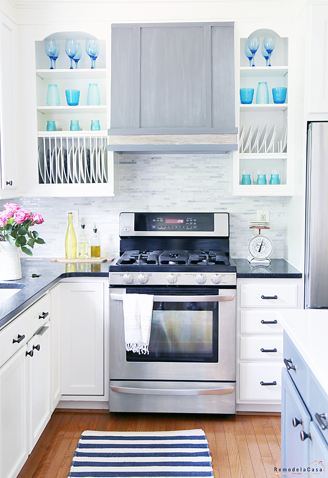 White kitchen with colorful decor and grey range hood