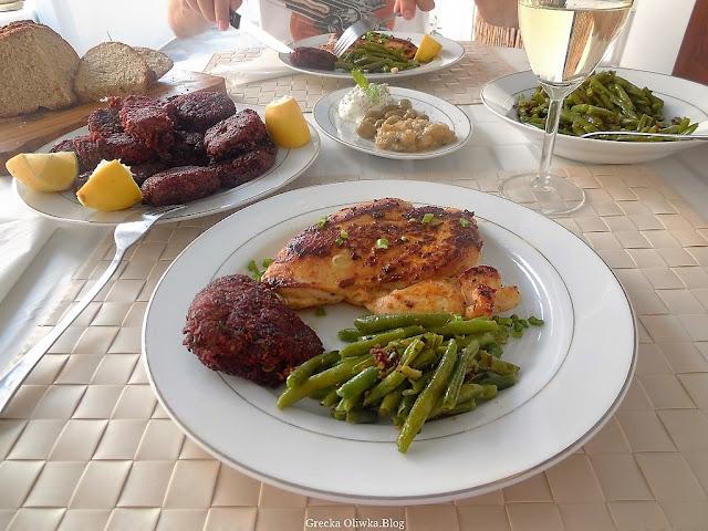 na stole talerz z kotletami z buraków, grecki chleb, tzatzyki, fasolka szparagowa, kieliszek wina