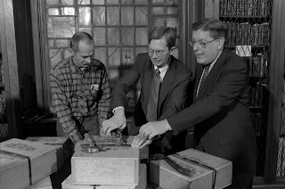 A photograph of three men opening a wooden box.