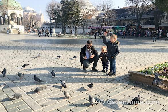 çocuklarla Sultan Ahmet meydanında güvercinleri beslerken, İstanbul