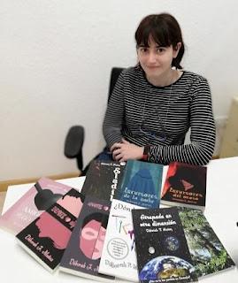 Déborah F Muñoz con sus libros en Ademm