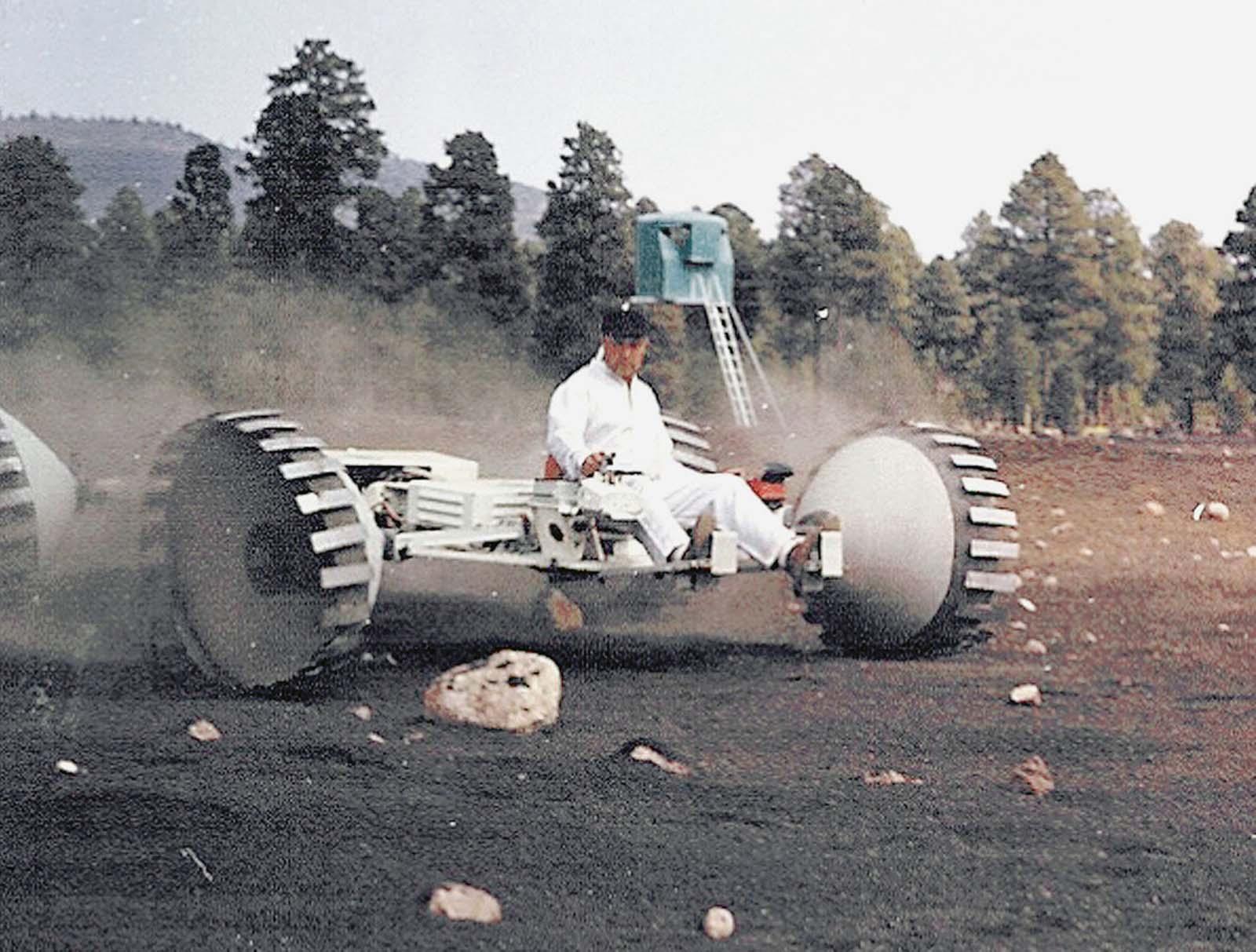 A Grumman Aircraft Engineering Corporation lunar-rover concept vehicle navigates boulders with a Grumman engineer driving.
