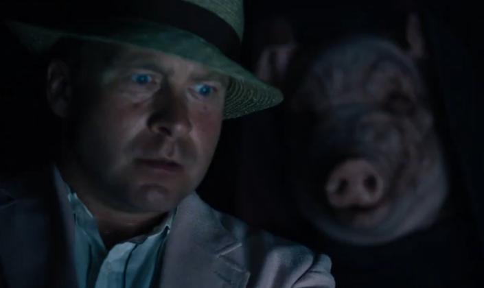 Primeiro plano: Homem branco de olhos azuis, sem barba, olha para frente com pavor. Ele usa chapéu estilo social e terno. Atras dele em meio a escuridão uma figura encapuzada usando uma máscara realista de porco, que está suja de terra.