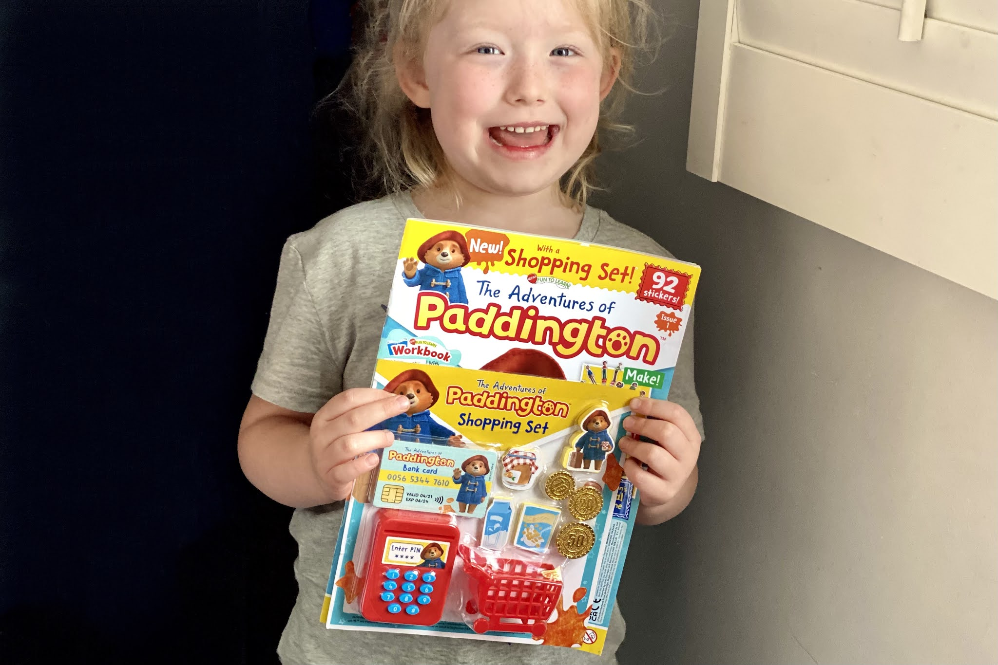 A happy looking 5 year old holding The Adventures of Paddington Bear magazine in front of her ready to review it