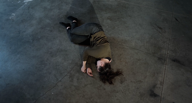 White woman lying in fetal position on a concrete floor wearing black jeans and green top, image looks down