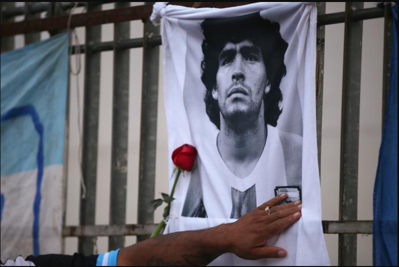 Una rosa es colocada junto a una imagen de Diego Maradona, en el Obelisco de Buenos Aires, al reunirse los fanáticos para lamentar su muerte / VOA