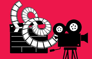 Black movie projector on pink background