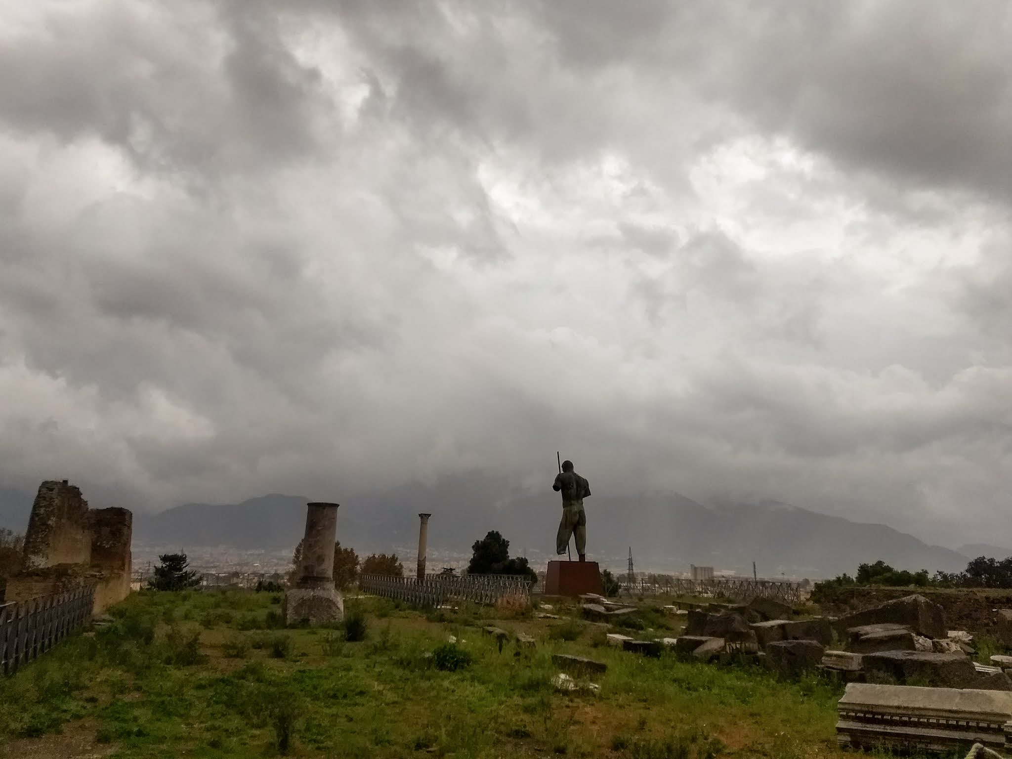Ruins of Pompeii on a cloudy day with obscured Mount Vesuvius.