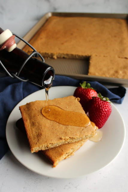 pouring homemade maple syrup over slices of banana sheet pan pancake