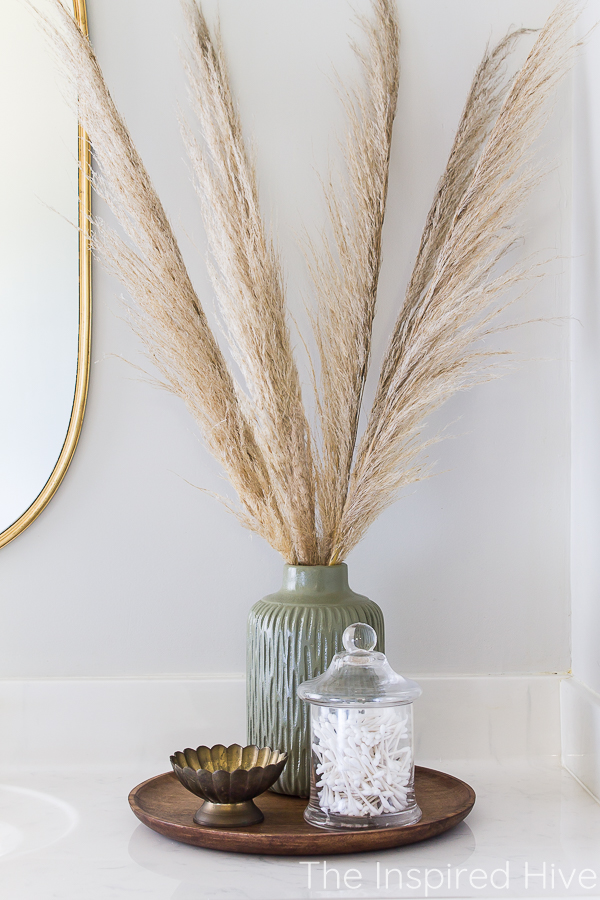 Wooden vanity tray with vintage brass bowl, jar of cotton swabs, and green vase with pampas grass