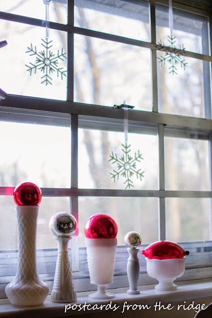 Milk glass, vintage mercury glass, and snowflakes. Lots of other great Christmas decorating ideas on this site.
