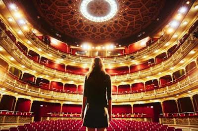 Mulher olhando para uma plateia vazia