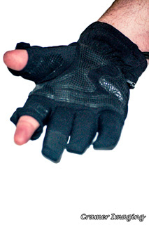 Photograph of a black photographer's glove with removable thumb and index finger sections on white background by Cramer Imaging