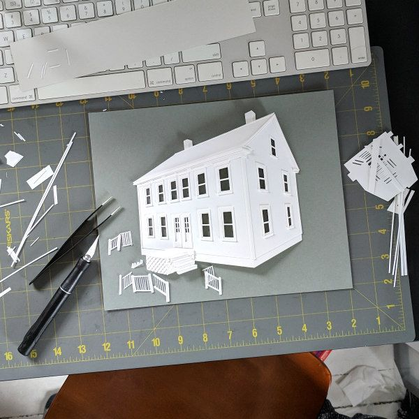 cutting mat with tools and cut paper house in progress