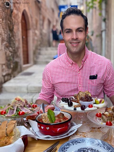 Handsome man eating dinner outdoors