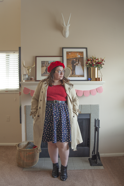 An outfit consisting of a red beret, classic khaki trench coat over a red sweater tucked into a navy blue, red and yellow dotted knee length skirt and black chelsea boots.