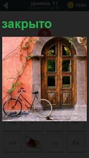 Закрытая дверь в здание и рядом стоит велосипед. По стене ползет зеленое растение
