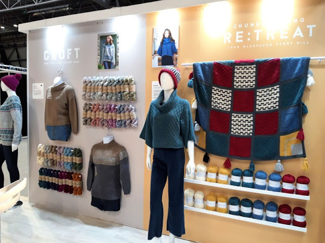 Image shows WYS The Croft yarn skeins hanging on a wall next to mannequins wearing jumpers.  To the right is a mannequin wearing a teal blue jumper and a black, white and red hat.  On the wall is a blanket in the same colours