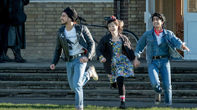 Aaron Phagura, Nell Williams, and Viveik Kalra run through the streets of Luton, England in a movie still for the drama Blinded by the Light