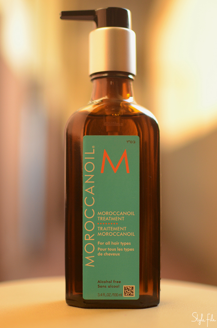 Image of the Moroccan Oil Treatment Original bottle against a brown background in sunlight