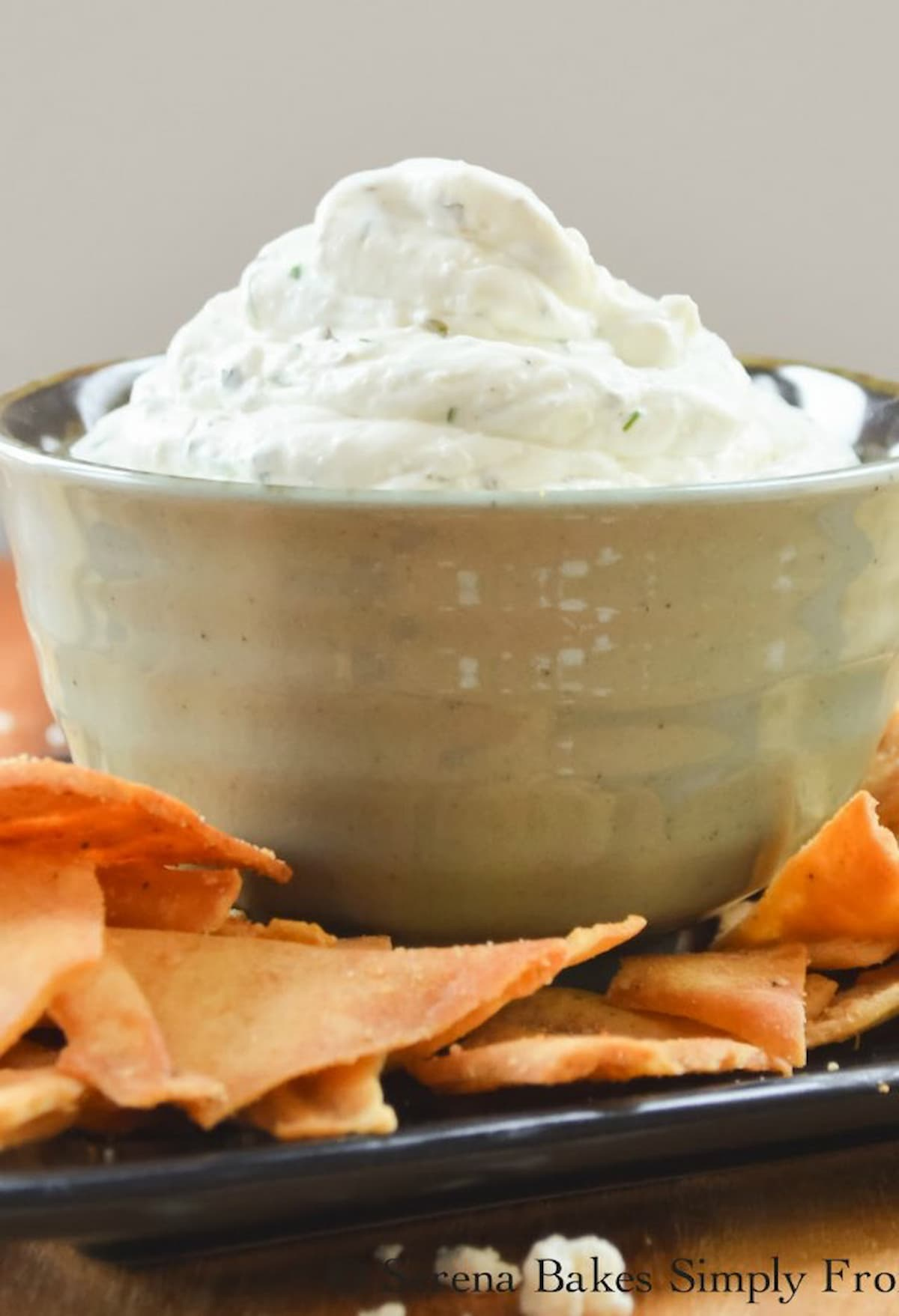 Greek Feta Dip in a small grey bowl with pita chips spread around the edge.