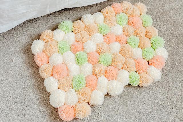 A multi-coloured pom-pom rug on the floor.