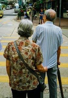 信号待ちしている老夫婦で、妻が夫のシャツに後ろから右手でしがみ付いている