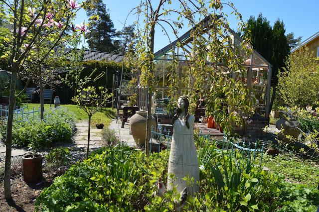 En solrik dag i Cornelias Verden - Foran drivhuset står Cornelia, et kunststykke